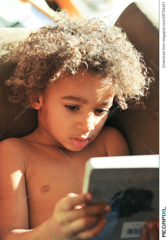 Young Mixed Race Boy With Curly Hair Reading Stock Photo 28704451 Megapixl
