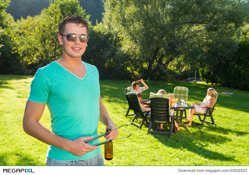 Man Holding Tongs And Wine Bottle At Garden Party Stock Photo ...