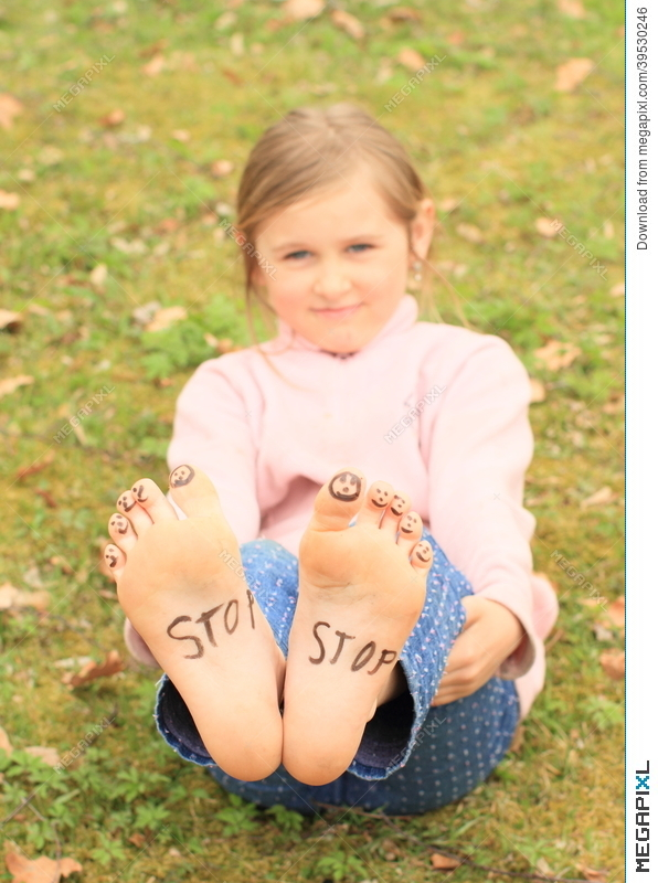 girl with smileys on toes and sign stop on soles stock photo