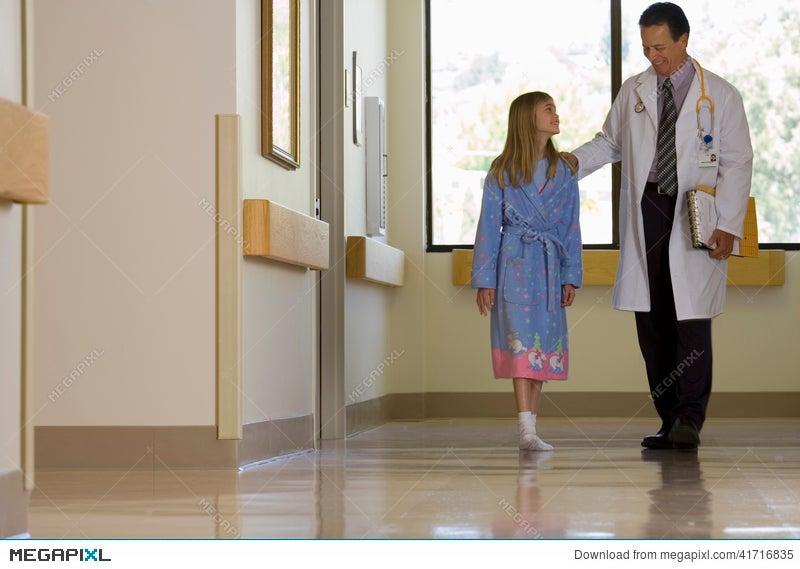 Doctor Walking With Patient In Hospital Corridor, Girl (10-12 ...
