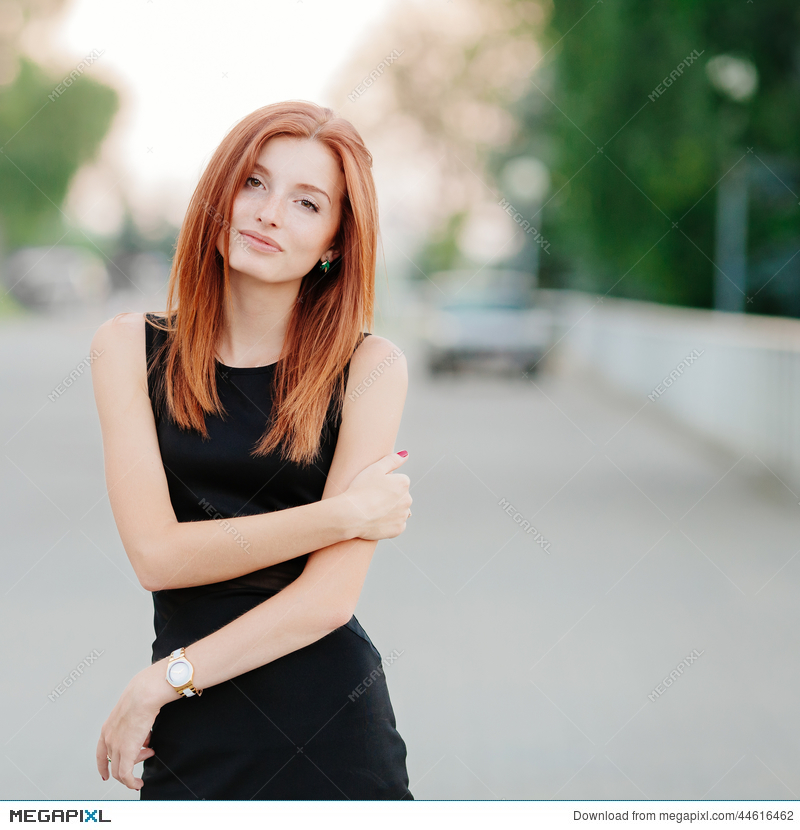 Emotive Cute Young Redhead Woman In A Black Dress Stock Photo