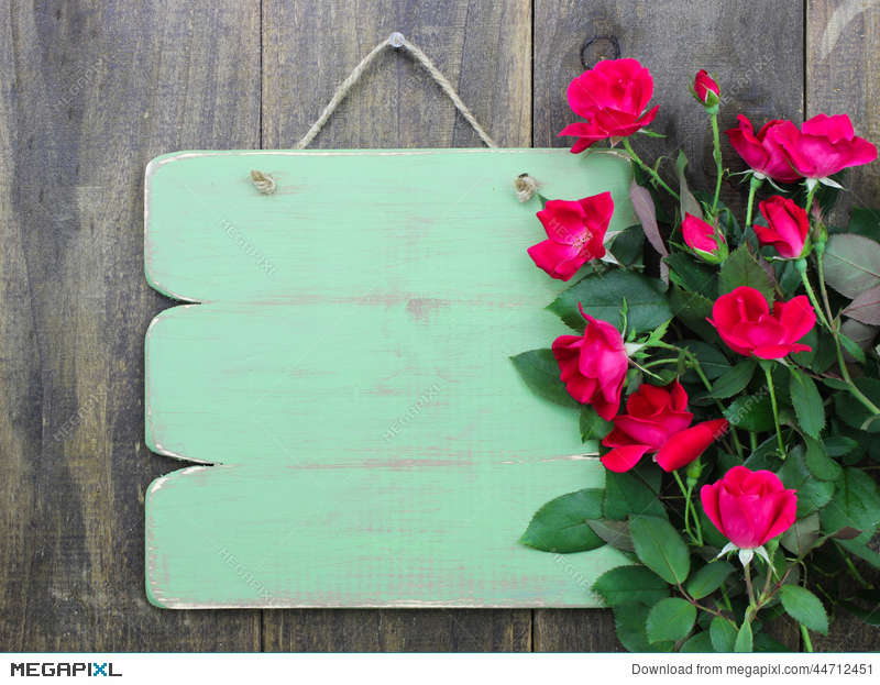 Distressed Blank Green Sign With Flower Border Of Red Roses Hanging On Rustic Wood Door