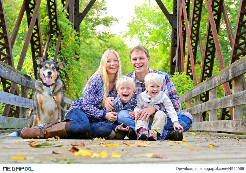 Portrait Of Happy Family And Dog Outside In Fall