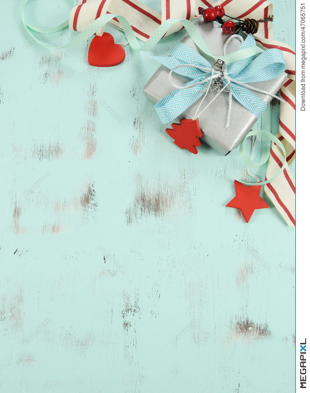 modern red and white christmas decorations on aqua blue wood background with silver gift