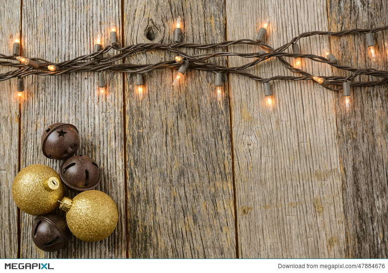Christmas Tree Lights With Rustic Wood Background And Gold Ornaments Bells