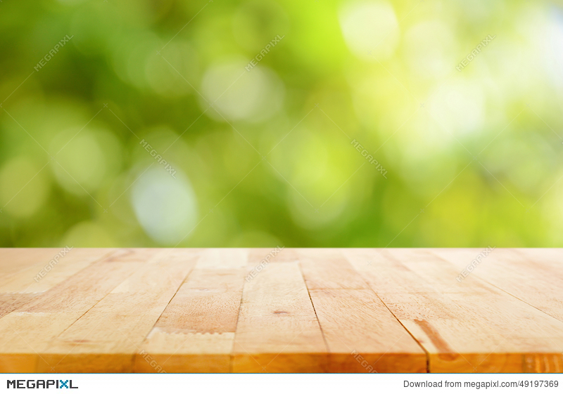 Wood Table Top On Bokeh Abstract Green Background Stock Photo