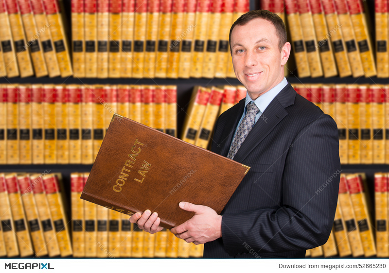 Young Lawyer With Law Books In The Background Stock Photo
