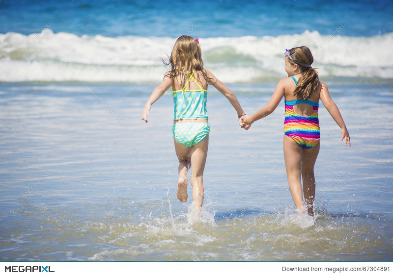 c0ec40ee549 Cute little girls playing at the beach together during summer vacation