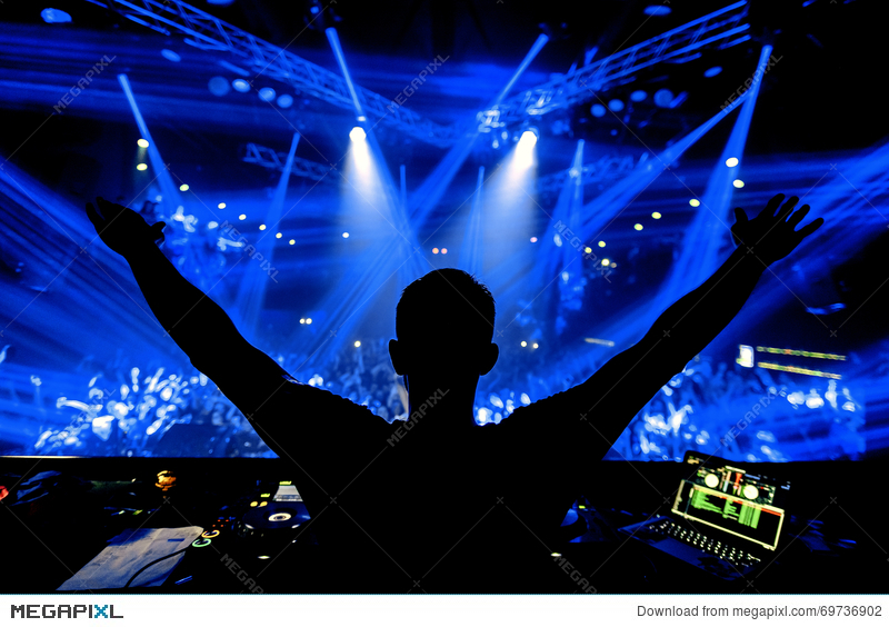 dj hands up at night club party under blue light with crowd of